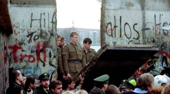 1989 - muren faller. Östtyska gränsvakter blickar in i Västberlin genom ett hål i muren.